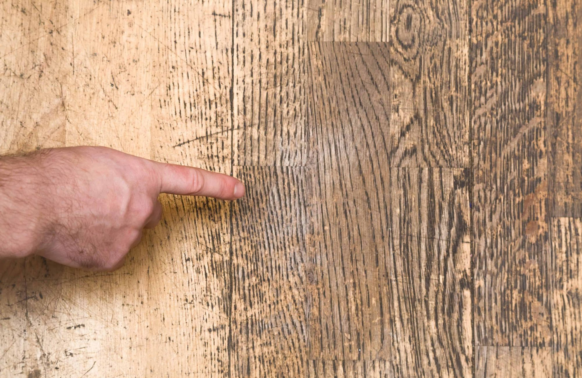 Man's hand pointing to the old scratched wooden floor in the room. Problems and solutions concept.