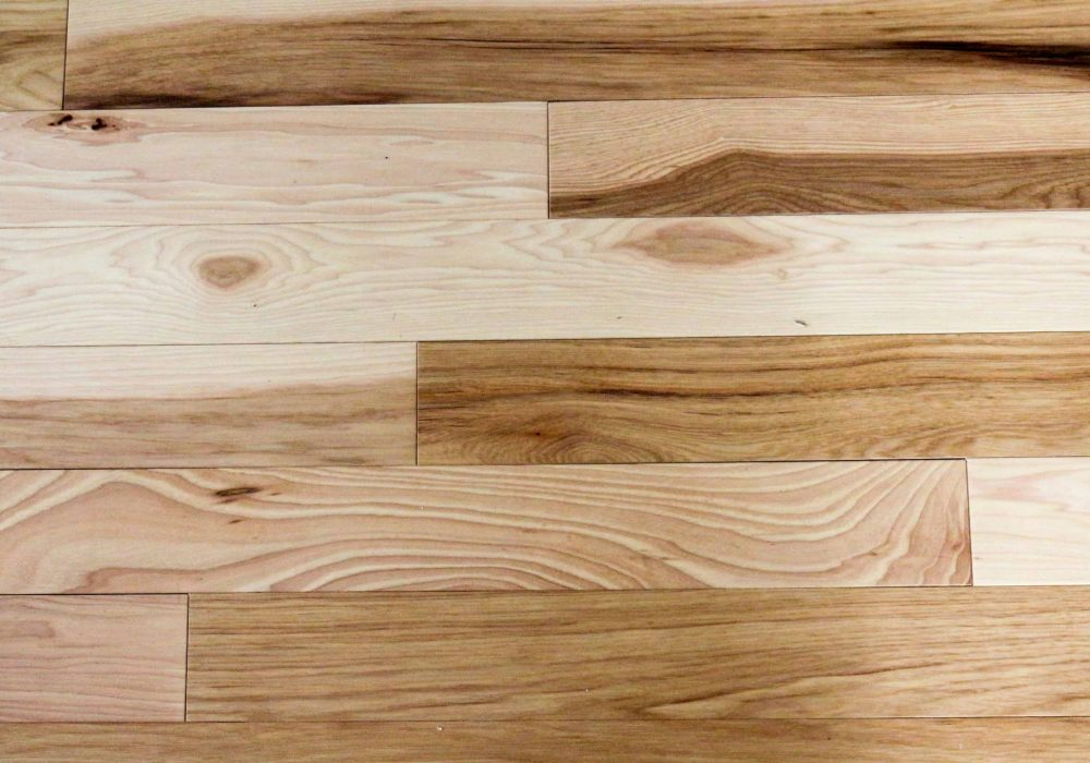 Natural hickory wood flooring with knots and grain.  Planks of the hardwood are horizontally oriented.